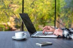 Personne travaillant au bureau en bois au téléphone de café d'ordinateur Photos libres de droits