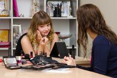 Personnel administratif en consultation avec l'artiste de maquillage de rouge à lèvres Image stock