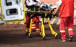 Personnel d'ambulance avec une civière sur une voie de sport images stock