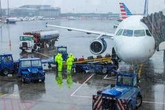 Personnel de piste d'aéroport manipulant des bagages un jour pluvieux à l'aéroport de LaGuardia se préparant au vol Image stock