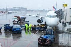 Personnel de piste d'aéroport manipulant des bagages un jour pluvieux à l'aéroport de LaGuardia se préparant au vol Images libres de droits