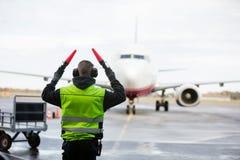 Personnel de piste signalant à l'avion sur la piste humide image stock