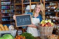 Personnel de sourire tenant le panneau organique de signe dans la section organique Image libre de droits