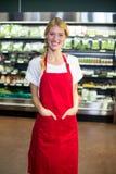 Personnel féminin de sourire se tenant avec des mains dans la poche dans la section d'épicerie Photo libre de droits