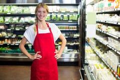Personnel féminin de sourire se tenant avec la main sur la hanche dans la section d'épicerie Photographie stock