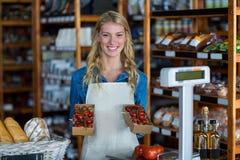 Personnel féminin de sourire tenant la boîte de la tomate-cerise dans le supermarché Photo stock