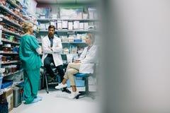 Personnel hospitalier discutant le médicament dans la pharmacie image stock