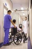 Personnel hospitalier poussant le patient dans le fauteuil roulant photographie stock libre de droits