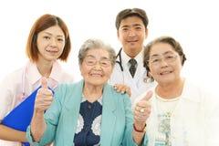 Personnel médical asiatique de sourire avec dames âgées Images libres de droits