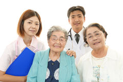 Personnel médical asiatique de sourire avec dames âgées Photo libre de droits
