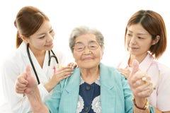 Personnel médical de sourire avec dame âgée Image libre de droits