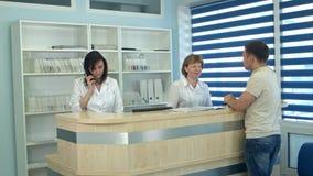 Personnel médical travaillant à la réception médicale occupée Photographie stock libre de droits