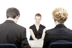 Personnel officers interviewing a candidate. Rear view of a male and female personnel officer interviewing an attractive smiling female candidate for a vacant stock photo