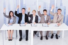 Personnel officers sitting with hands raised at table Royalty Free Stock Image