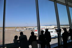 Personnes à l'intérieur d'aéroport de YVR observant l'avion d'Air Canada Images stock