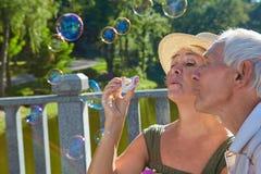 Personnes âgées avec le ventilateur de bulle photographie stock libre de droits