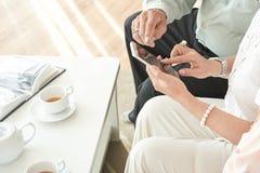 Personnes âgées employant l'appli mobile photos libres de droits