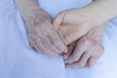 Personnes âgées et mains de jeune femme Images libres de droits