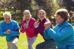 Personnes âgées exubérantes s'exerçant en parc Photos stock