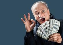 Personnes âgées heureuses avec le ventilateur de l'argent Photographie stock