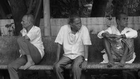 Personnes âgées trois s'asseyant sur le banc photos stock