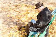 Personnes âgées une lecture se reposante d'homme à jambes en parc Photos stock