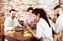 Personnes adultes à l'aide des smartphones à la table de café Image libre de droits