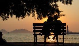 Personnes affectueuses sur le banc en silhouette Photo stock