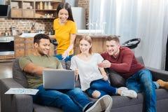 Personnes amicales heureuses s'asseyant sur le sofa et regardant l'ordinateur portable Photos libres de droits