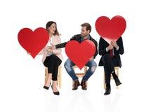 3 personnes assises tenant de grands coeurs rouges partagent l'amour image stock