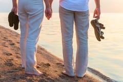 Personnes aux pieds nus avec les chaussures à disposition Photographie stock libre de droits