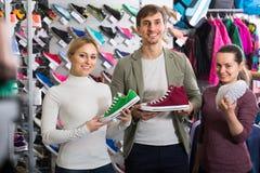 3 personnes avec des chaussures dans la boutique de sport Photo stock