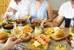 Personnes avec du vin blanc grillant au-dessus de la table servie avec la nourriture Photographie stock