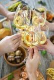 Personnes avec du vin blanc grillant au-dessus de la table servie avec la nourriture Images stock