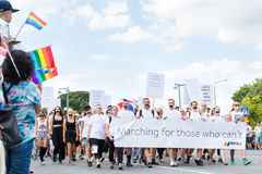 Personnes avec les bouches attachées du ruban adhésif marchant avec la bannière pendant Stockholm Pride Parade Photos libres de droits