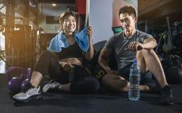 Personnes convenables dans la vitesse d'exercice se reposant ensemble sur le plancher d'un gymnase riant ensemble après une séanc photographie stock libre de droits