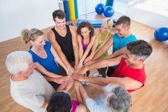 Personnes convenables empilant des mains au club de santé Image libre de droits