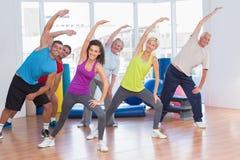 Personnes convenables faisant étirant l'exercice dans le gymnase Photo stock