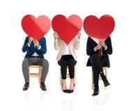 3 personnes couvrant leurs visages de grands coeurs rouges photo libre de droits