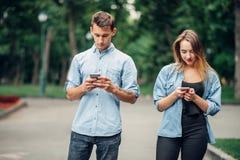 Personnes dépendantes de téléphone, couples en parc d'été photo libre de droits