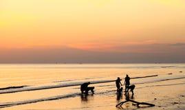 Personnes d'ombre au coucher du soleil le long de la côte Photos stock