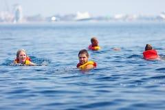 Personnes dans des gilets de sauvetage nageant en mer ouverte Photos stock