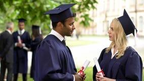 Personnes dans la robe et des chapeaux scolaires avec des diplômes dans des mains parlant, jour  photographie stock