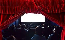 Personnes dans le cin?ma observant un film ?cran blanc vide vide Rideau rouge en théâtre sur le premier plan image stock