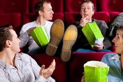 Personnes dans le théâtre de cinéma mangeant le porcorn Photo stock
