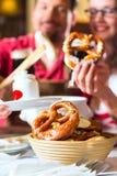 Personnes dans Tracht bavarois mangeant dans le restaurant ou le bar Images stock