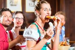 Personnes dans Tracht bavarois mangeant dans le restaurant ou le bar Photographie stock