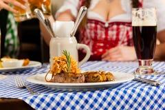 Personnes dans Tracht bavarois traditionnel mangeant dans le restaurant ou le pub Image stock