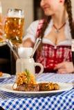 Personnes dans Tracht bavarois traditionnel mangeant dans le restaurant ou le pub Images libres de droits