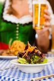 Personnes dans Tracht bavarois traditionnel mangeant dans le restaurant ou le pub Photo stock